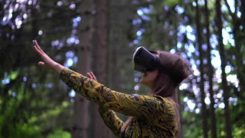 Woman in VR headset looks up at the objects in virtual reality reaching out Live Action