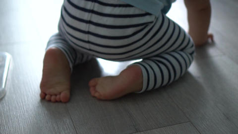 Barefooted baby in striped pants crawles on a floor. Shallow depth of field Footage