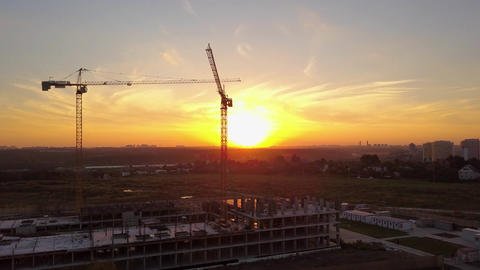 Aerial shot of cranes over building under construction against bright sunset sky Image
