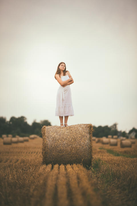 Beautiful Girl on Hay Bales in the Fields フォト
