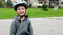 Child (a little boy) smiles on bike - in the background houses and nature (grass Footage