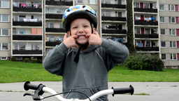 child (a little boy) grimaces - child with bike - house in background Footage
