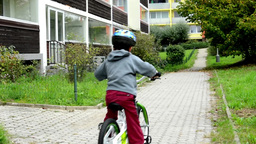 Child (a little boy) rides bike - in the background houses and nature (grass and Footage