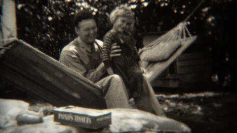 1943: Dad and daughter swinging on hammock with Pond's Tissues box Footage