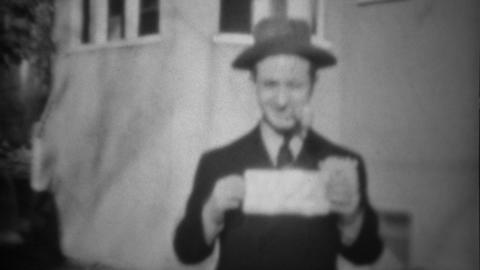 1939: Man holding sign with pipe in mouth walks past classic car Live Action