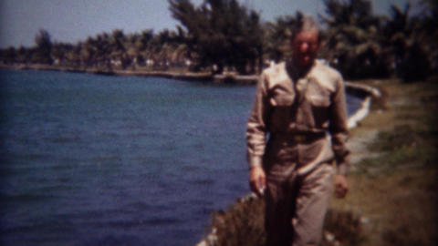 1944: Army soldier stumbles and salutes on sunny tropical water bay Footage