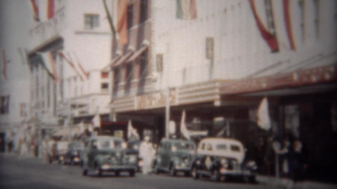 1944: Downtown mainstreet city patriotic flags waving above the street Live Action