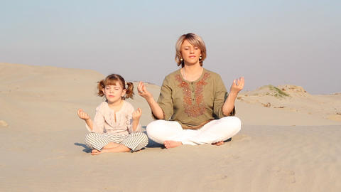 mother and daughter meditating in desert Footage