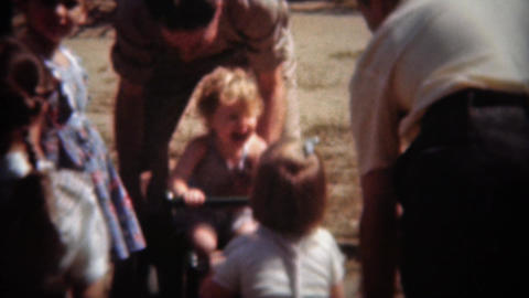 1944: Kids play on seesaw park toy ride with help of father parents Footage