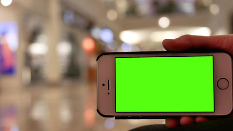 Motion of people holding green screen phone with blur motion of people shopping Footage