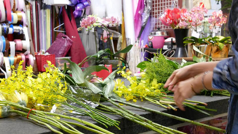 Motion of florist prepares a bouquet of flowers for customer, close up on hand Footage
