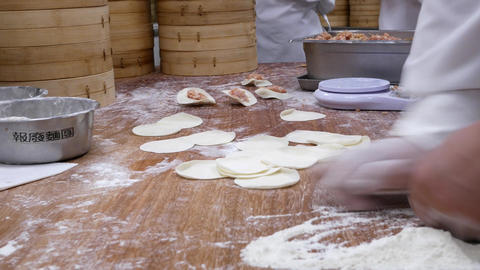 Pan shot of people are kneading the dough and shaping it with their hands to Footage