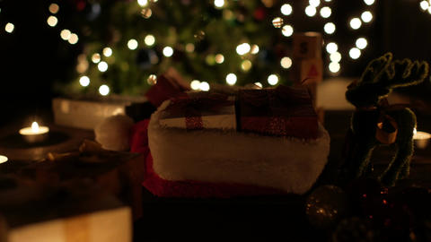 Christmas gift boxes in santa hat with reindeer and candle on bokeh lights ビデオ