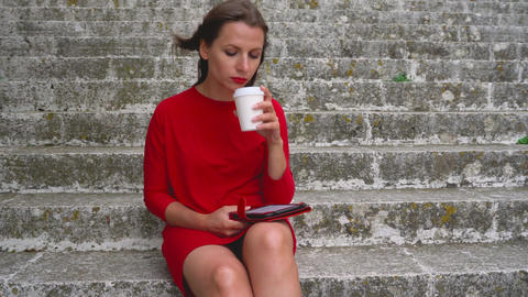 Woman reading an e-book sitting on the steps outdoors Footage