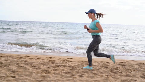 Athletic woman running along the beach Archivo
