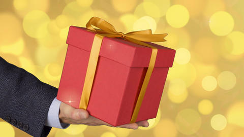 Male man hand holds red gift box with gold bow. Celebrate eve present gift box Live Action