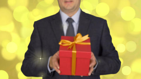 A man in a business suit with a tie is holding a red gift box. A man gives a Footage