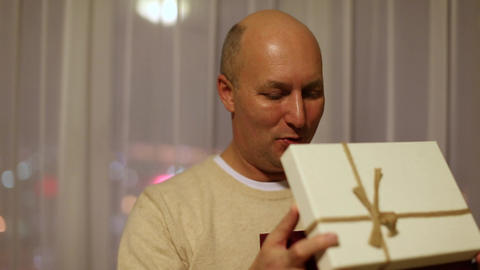 Happy adult caucasian man open gift box. Flickering lights at his face. Orange Footage