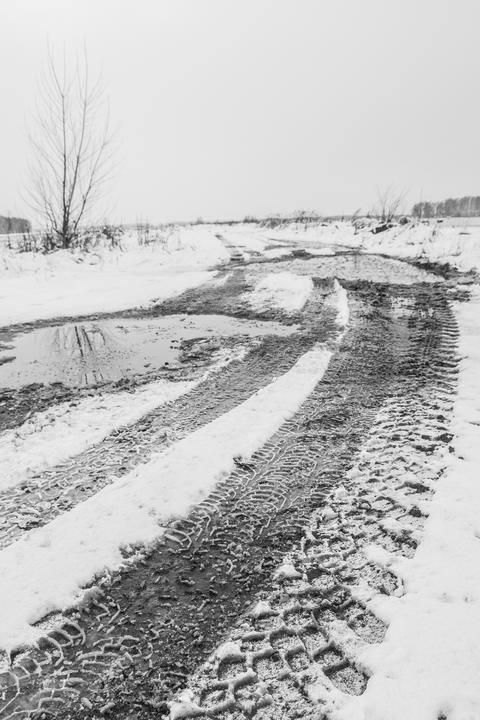 Traces of the tread of the car's wheels on the countryside snow-covered road フォト
