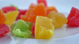 Colorful cubes candied fruit falling on white plate Live Action