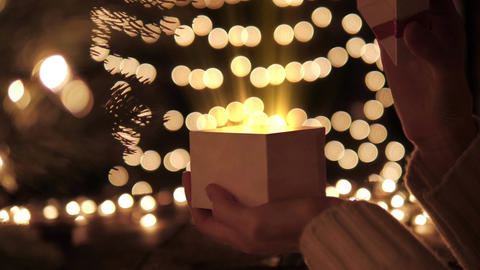 Woman open the gift box with golden light magic on bokeh lights background Live Action
