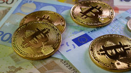 Gold Bitcoin BTC coins rotating on bills of euro Image