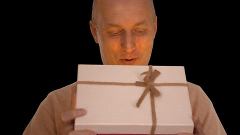 Happy adult caucasian man get gift box. Man looking to camera and smiling 画像