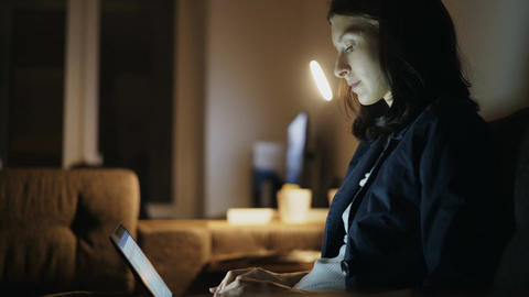 Young concentrated woman working at home in night time using laptop computer and Footage
