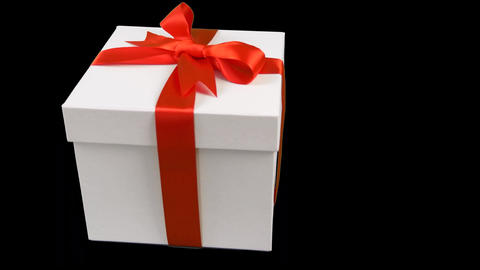White gift box with red ribbon bow rotate at transparent background. Alpha Live Action