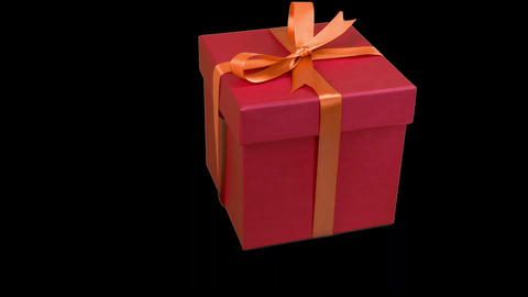 Red gift box with yellow gold ribbon bow rotate at transparent background. Alpha Live Action