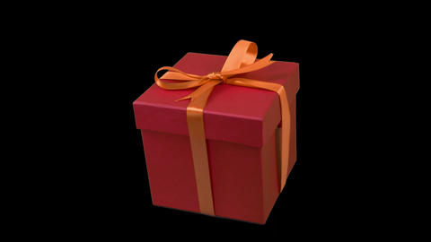 Red gift box with yellow gold ribbon bow track to right at transparent Live Action