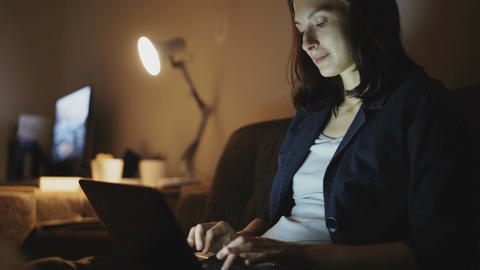 Young cheerful woman working in office at night using laptop computer and typing ビデオ