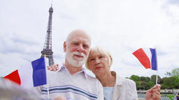 Senior couple with French flags near Eiffel Tower doing selfie. Smiling tourist Archivo