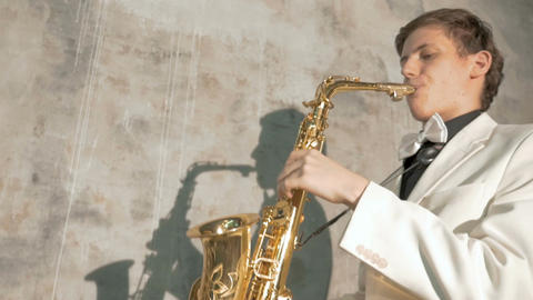 A musician in a white suit plays the saxophone. close-up Footage
