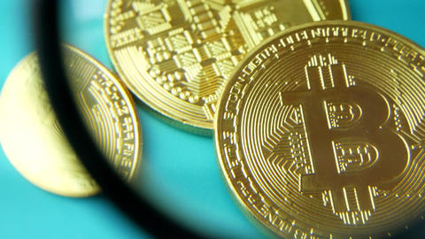 Gold Bitcoin BTC coins and magnifying glass or loupe 画像