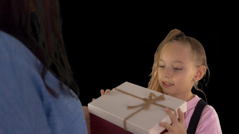 Mom gives my daughter a gift box. The girl opens the box and looks inside. Her Bild