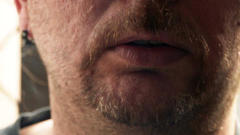 Unshaven man inhaling and exhaling cigarette front view Footage