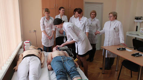 the interns studying how to set the sensors for electrocardiogram on body Live Action