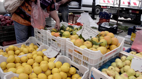 Woman Choose From At The Market Stall Fruit, Fresh Oranges Which Puts Them In A  stock footage