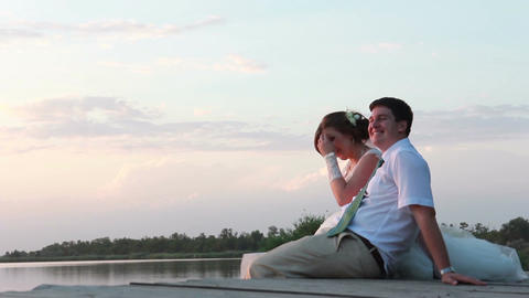 Newlyweds sitting on the wharf near the lake at sunset Footage