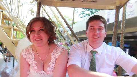 the bride and groom ride on the carousel on the wedding day Footage
