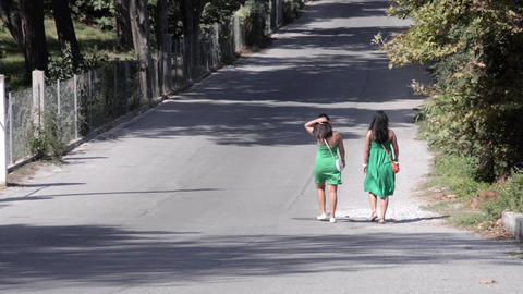 Girls dressed in green dress walking on a street where a few cars circulating 1 Footage