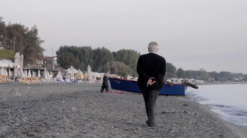 Old man who was walking on the beach going towards a boat pulled ashore 6a Footage