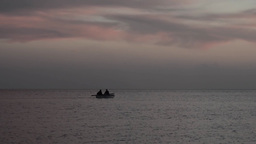 Rowing boat that leads two people are heading out to sea 4b Footage
