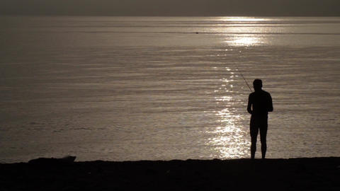 Silhouette of a man came out from fishing at ocean in the early hours of the mor Footage
