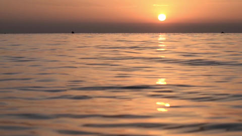 Sunrise at the seashore which float a few fishing boats 0 Footage