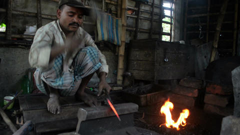 Wide shot of an Indian blacksmith making a sickle Footage