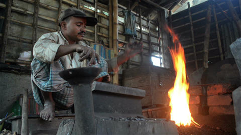 A candid wide shot of an Indian blacksmith doing his daily job Footage
