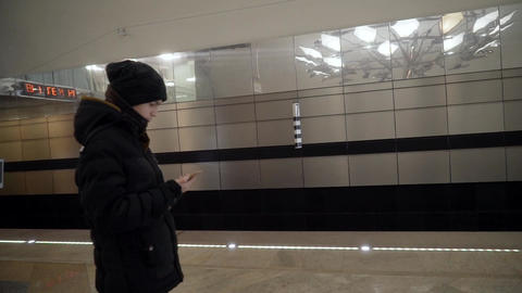 A young man with a phone in his hands is waiting for the train in the subway Footage