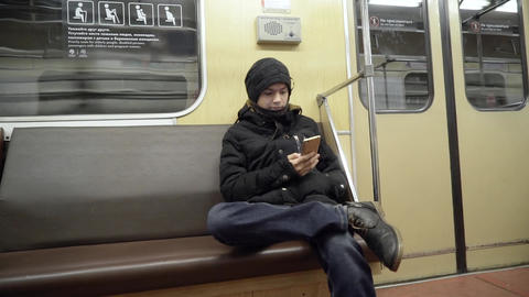 A guy in winter clothes in the subway using a smartphone. The young man is Footage